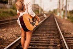 Kvinna med en gitarr på en järnväg arkivfoton