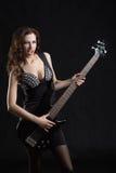 Kvinna med en gitarr på etappen Royaltyfri Foto