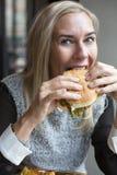 Kvinna med en hamburgare Arkivfoto