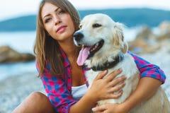 Kvinna med en hund på en gå på stranden Arkivbild