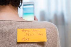 Kvinna med en klibbig anmärkning på henne tillbaka på April Fools Day Arkivfoto