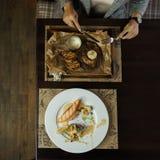 Kvinna med en kniv och gaffelsnitt en köttbiff med grönsaker i en restaurang Äta lunch avbrottet Begreppet av en sund matställe arkivfoto