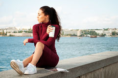 Kvinna med en kopp av cofee nära havet Arkivbild