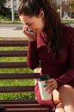 Kvinna med en kopp av den talande telefonen för cofee Fotografering för Bildbyråer