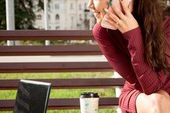 Kvinna med en kopp av den talande telefonen för cofee Arkivfoto