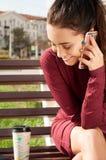 Kvinna med en kopp av den talande telefonen för cofee Royaltyfri Bild