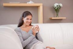 Kvinna med en kopp av kaffe på sofaen royaltyfri fotografi
