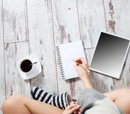 Kvinna med en kopp kaffe, en notepad och en minnestavla Arkivbild