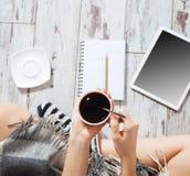 Kvinna med en kopp kaffe, en notepad och en minnestavla Arkivfoto