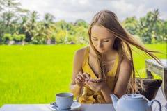 Kvinna med en kopp te på kaféverandan nära risterrasserna på Bali, Indonesien royaltyfria bilder