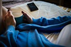 Kvinna med en kopp te som lyssnar till musik i säng Fotografering för Bildbyråer