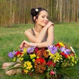 Kvinna med en korg av blommor Royaltyfria Bilder