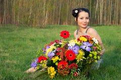 Kvinna med en korg av blommor Royaltyfri Fotografi