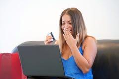 Kvinna med en kreditkort hemma En ung flicka köper direktanslutet En kvinna rymmer en kreditkort och använder en bärbar dator Beg arkivbilder