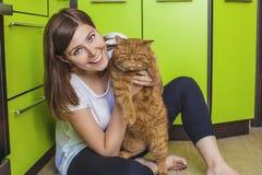 Kvinna med en ljust rödbrun katt i henne armar som kelar på köket arkivbild
