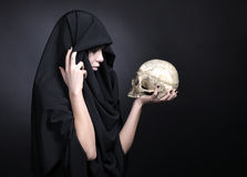 Kvinna med en mänsklig skalle i black Royaltyfri Bild