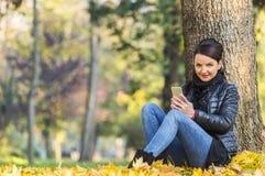 Kvinna med en mobil i en skog i hösten Arkivbilder