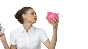Kvinna med en piggybank och kontant in henne händer Royaltyfri Fotografi
