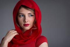 Kvinna med en röd sjalett på hennes huvud royaltyfri fotografi