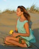 Kvinna med en ros på sand Arkivfoto