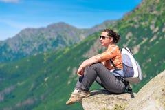 Kvinna med en ryggsäck som vilar, sitter på en sten och beundrar t Royaltyfria Foton