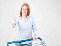 Kvinna med en shoppingvagn som ger upp tummar Arkivfoton