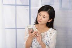 Kvinna med en smart telefon fotografering för bildbyråer