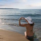 Kvinna med en solhatt på kusten, former med hennes fingrar ett H fotografering för bildbyråer