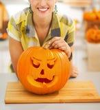 Kvinna med en stor orange pumpaStålar-NOLLA-lykta i kök Royaltyfri Fotografi