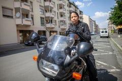 Kvinna med en svart hjälm på en moped royaltyfria bilder