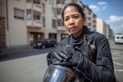 Kvinna med en svart hjälm på en moped arkivbild