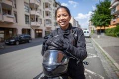 Kvinna med en svart hjälm på en moped arkivfoton