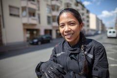 Kvinna med en svart hjälm på en moped royaltyfri foto