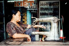 kvinna med en sy maskin framme av hennes väntande på klienter för lager royaltyfri bild