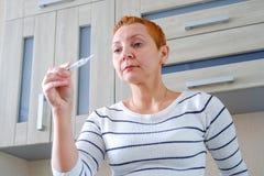 Kvinna med en termometer i hennes hand Högstämd kroppstemperatur arkivfoto