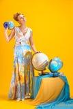Kvinna med en världskarta och jordklot Royaltyfri Bild