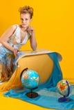 Kvinna med en världskarta och jordklot Royaltyfri Foto