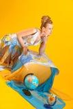 Kvinna med en världskarta och jordklot Royaltyfria Bilder