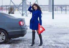 Kvinna med en varningstriangel i händerna av väntande på hjälp nära hennes bil Arkivfoton