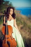 Kvinna med en violoncell i träna Arkivbilder