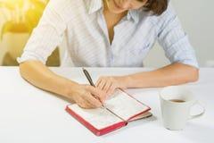 Kvinna med ett anteckningsboksammanträde på en tabell Arkivfoton