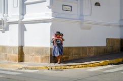 Kvinna med ett barn på hennes korsa tillbaka gatan i Bolivia Arkivbild