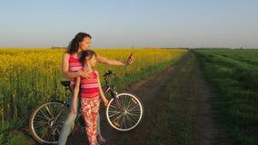 Kvinna med ett barn som gör selfie i natur En lycklig moder med hennes dotter fotograferas i bygden cyklister stock video