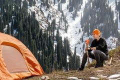 Kvinna med ett exponeringsglas av te eller kaffe nära ett turist- tält på ett stopp i bergen mot en bakgrund av dentäckte skogen  arkivfoton