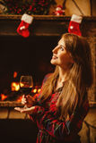 Kvinna med ett exponeringsglas av vin vid spisen Ung attraktiv wo royaltyfria foton