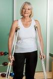 Kvinna med ett halsstag genom att använda kryckor Royaltyfri Foto