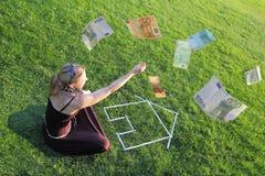 Kvinna med ett hus och pengar Arkivbild