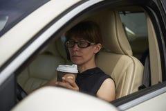 Kvinna med ett kaffe, medan köra bilen Royaltyfri Foto