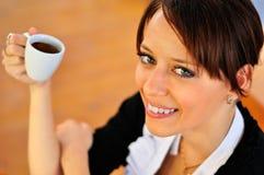 Kvinna med ett kaffe på träbakgrunden. Fotografering för Bildbyråer