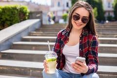 kvinna med ett limonadekoppsammanträde på trappan och texten på hennes smartphone Arkivfoton